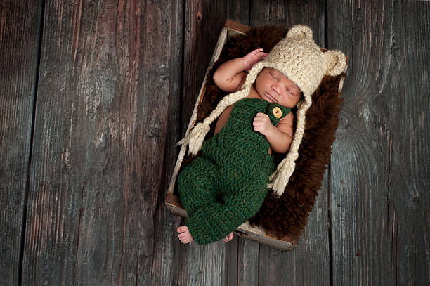 Newborn Baby Boy Wearing a Bear Hat Portrait of a newborn baby boy wearing crocheted green overalls and bear hat. He is sleeping in an old wooden crate. Shot in the studio on a rustic wood background. newborn animal stock pictures, royalty-free photos & images