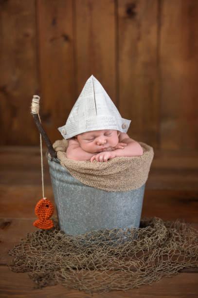 Newborn Baby Boy Wearing a Paper Hat stock photo