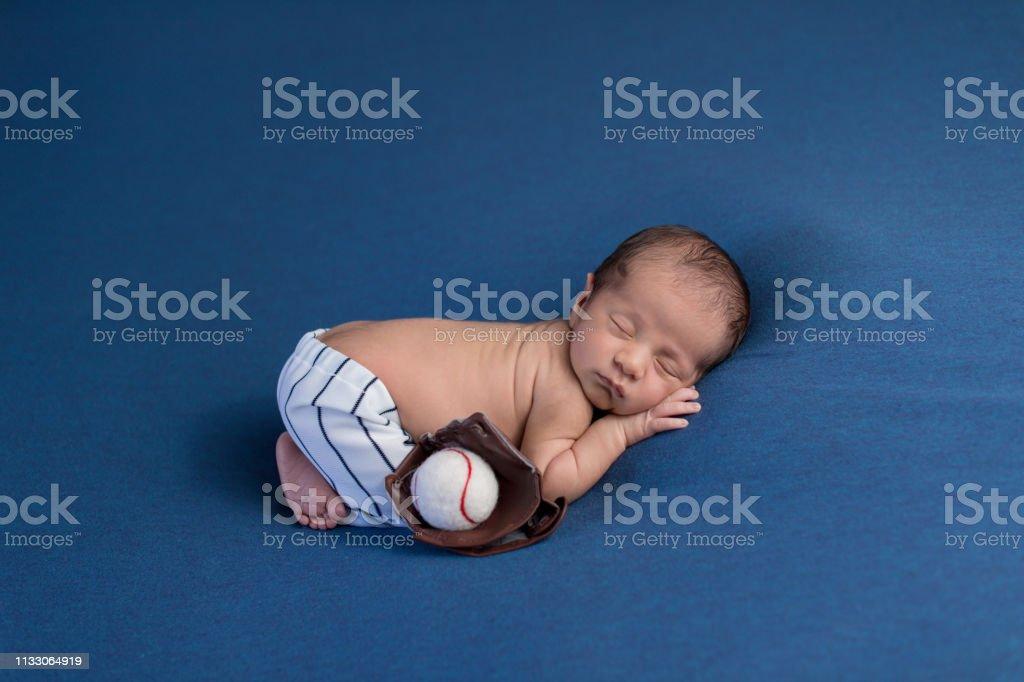 A week old, sleeping, newborn baby boy wearing baseball uniform pants...