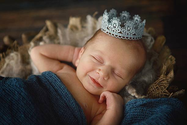 Newborn Baby Boy Wearing Crown A newborn baby boy smiles as he wears a silver crown. A prince is born!  royalty stock pictures, royalty-free photos & images
