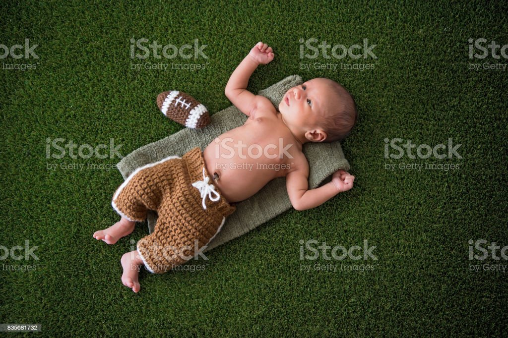 Newborn Baby Boy Wearing Football Uniform stock photo