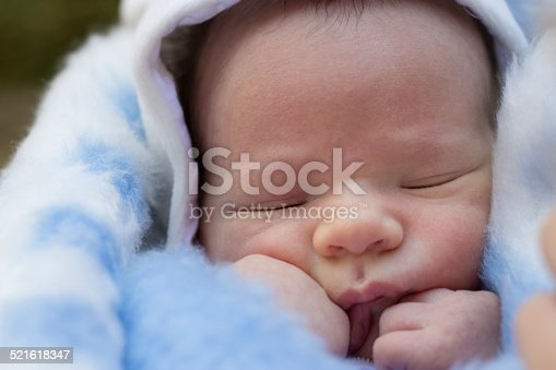 177414958istockphoto Newborn baby boy  wrapped in blanket 521618347
