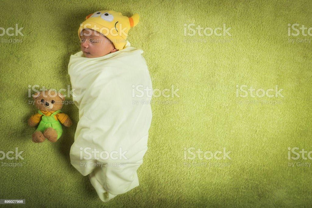Pasgeboren babyjongen verpakt in swaddle met teddybeer foto