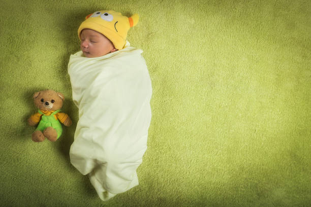 Newborn baby boy wrapped in swaddle with teddy bear View directly from above of a 10-day old newborn Eurasian baby boy wrapped in a swaddle with a small teddy bear sitting by his side. Studio shot with copy space provided for text. baby blanket stock pictures, royalty-free photos & images