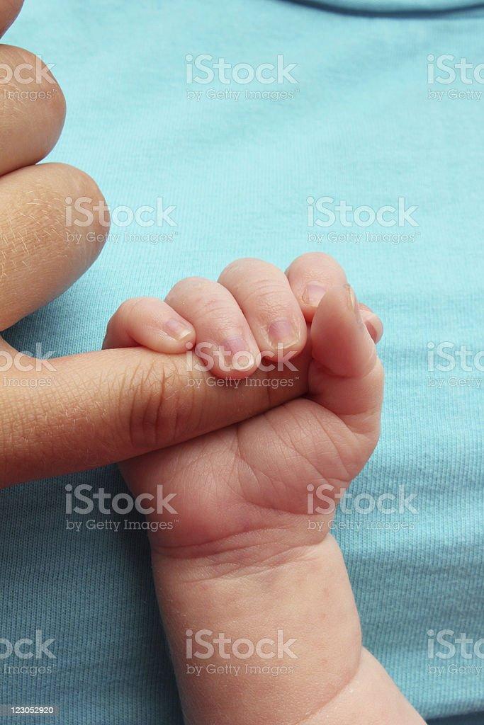 Newborn baby clutching madres dedo - foto de stock