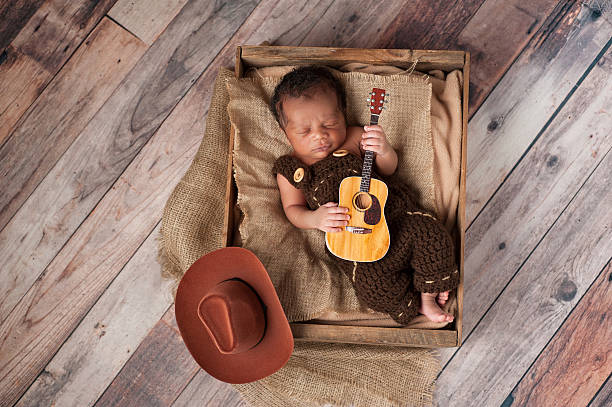 Newborn Baby Cowboy Playing a Tiny Guitar A two week old baby boy wearing crocheted overalls and playing a tiny acoustic guitar. He is lying in a wooden crate lined with burlap. Shot in the studio on a rustic, wood background. bib overalls stock pictures, royalty-free photos & images