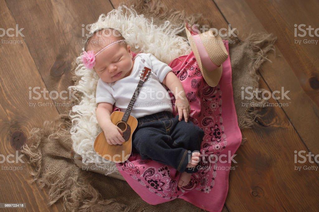 Vaquera bebé tocar una pequeña guitarra - foto de stock