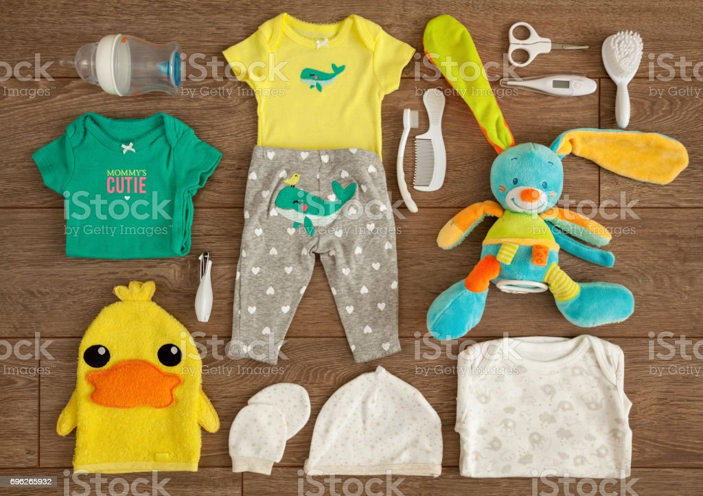 Newborn Baby Essential Stuff and Accessories in a Flat Lay Composition on Wooden Table stock photo