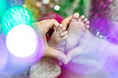 Newborn baby feet in the mother's hands. New Year's lights are around.