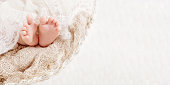 istock Newborn baby feet on knitted plaid. Closeup picture. Copyspace 1038646696