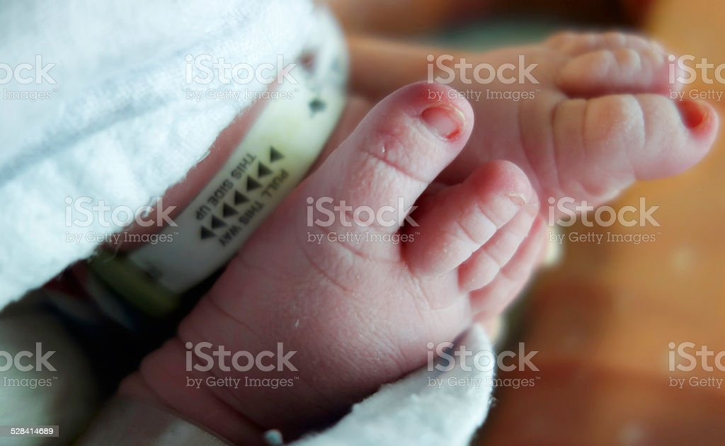 Newborn Baby Feet with Security Tags stock photo
