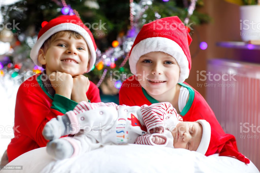 e1b9a6c444a7 Newborn baby girl and two older brothers kid boys in Santa hat near  Christmas tree - Stock image .