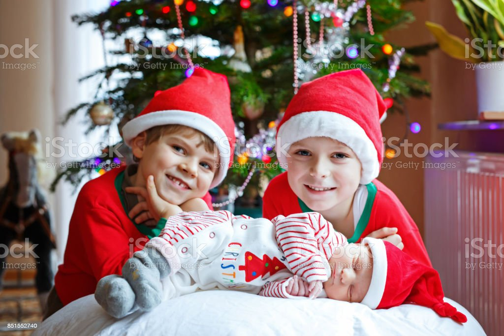 Newborn baby girl and two older brothers kid boys in Santa hat near Christmas tree stock photo