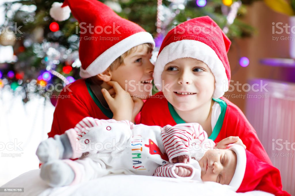 Newborn baby girl and two older brothers kid boys in santa hat near christmas tree royalty