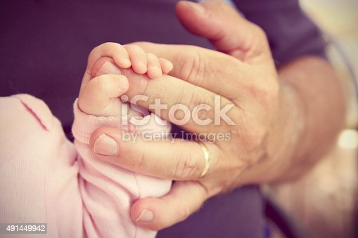 Close up on the Hand of a newborn baby girl holding the finger of her Grandpa lovingly. VIntage style Color.
