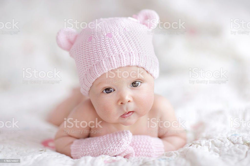 newborn baby girl in pink knitted bear hat stock photo
