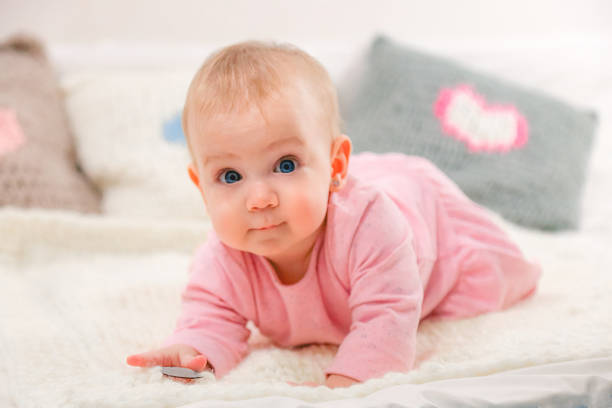 Newborn baby girl in pink Newborn baby girl in pink on knitted blanket and pillows with hearts. wrapped in a blanket stock pictures, royalty-free photos & images