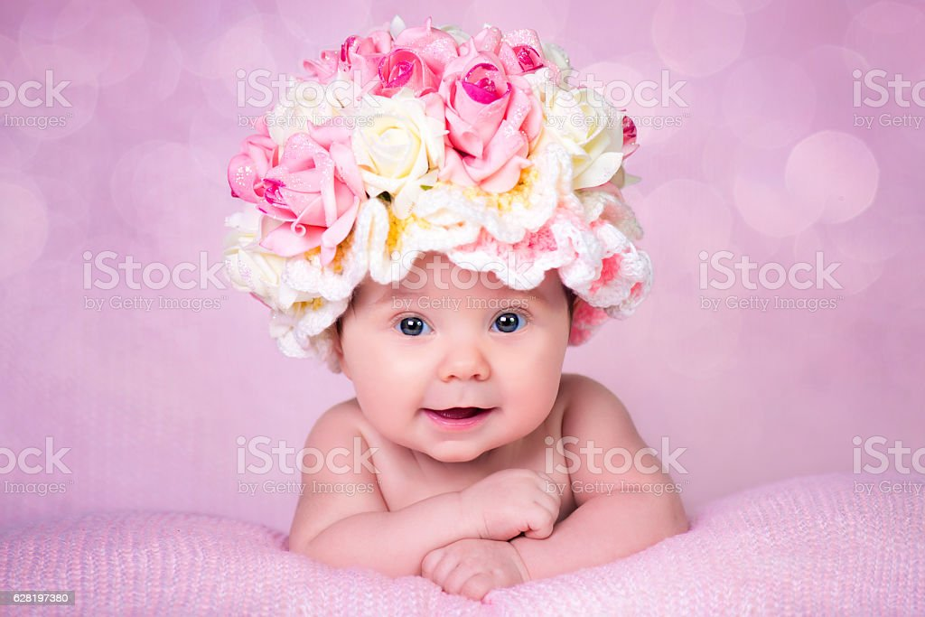 Newborn baby girl in the hat rose smiles. Portrait on стоковое фото