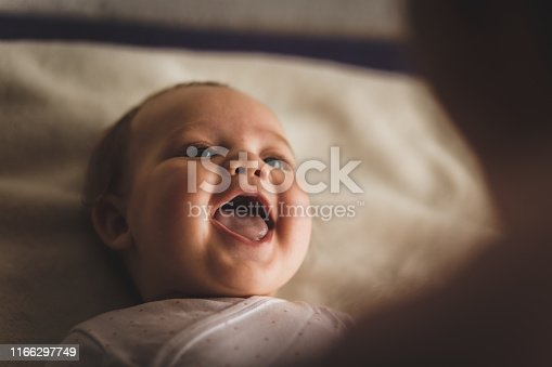 High angle view of cheerful newborn baby girl lying down on the bed and laughing while her mother, that is blurred in foreground, is playing with her.
