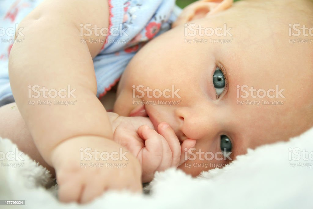 Newborn Baby Girl Laying Down Sucking Her Thumb stock photo