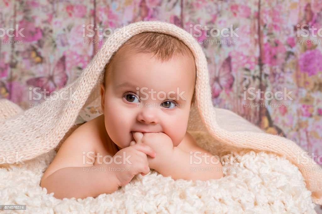 newborn baby girl lying on a bed with pink flower background royalty-free stock photo