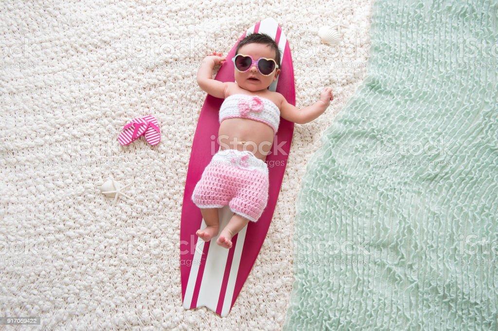 Newborn Baby Girl on Surfboard stock photo