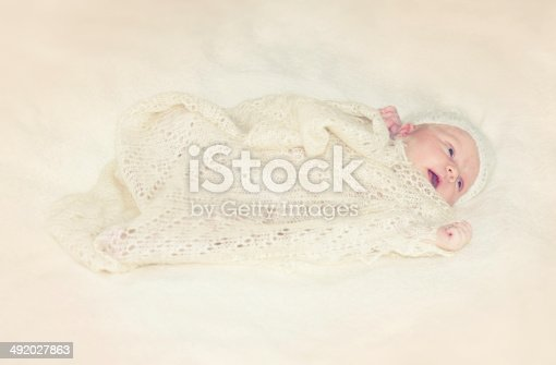 Three weeks old baby girl and crocheted blanket