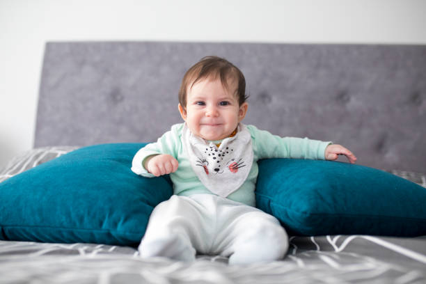 Newborn baby girl sitting with support pillows stock photo