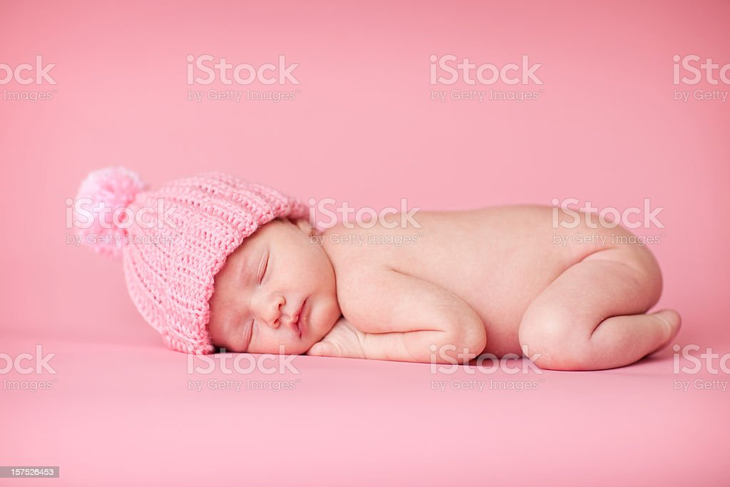 Newborn Baby Girl Sleeping Peacefully on Pink Background stock photo