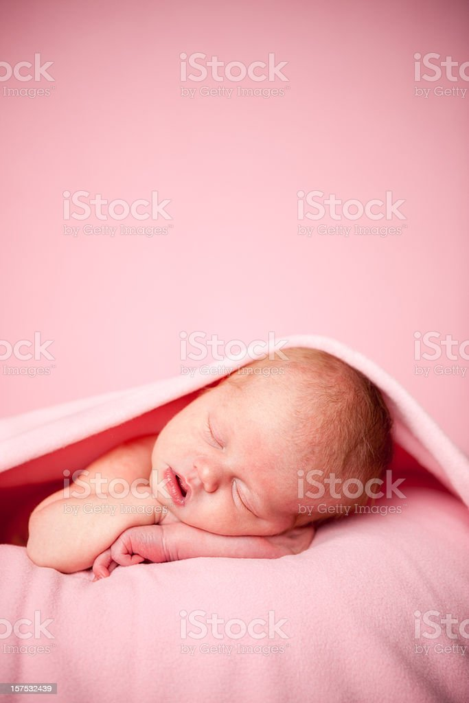 Newborn Baby Girl Sleeping Peacefully Under a Pink Blanket royalty-free stock photo