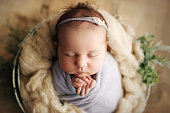 istock Newborn Baby Girl Swaddled in Prop Basket 1214276343