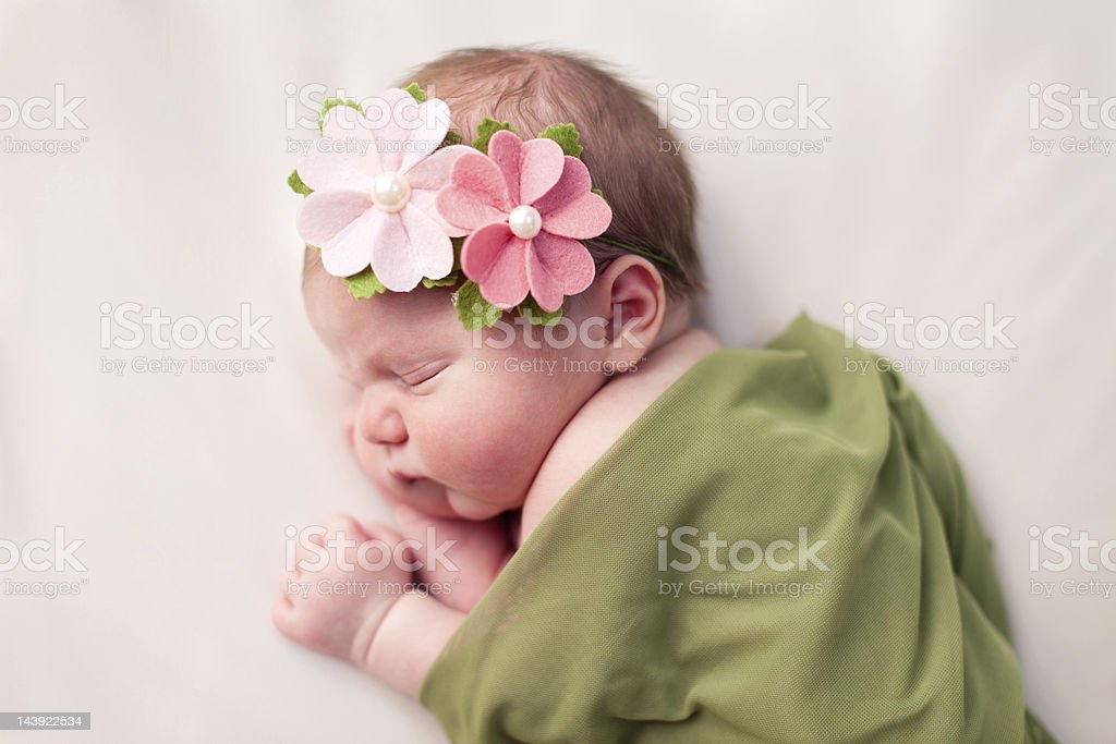Newborn Baby Girl Swaddled in Soft, Green Blanket Color image of a newborn baby girl wearing flowered headband and sleeping peacefully while swaddled in a soft, green blanket. Image is on white background. 0-1 Months Stock Photo