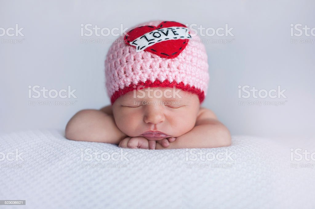 """Newborn Baby Girl Wearing a """"Love"""" Hat Portrait of a seven day old sleeping baby girl wearing a crocheted """"Love"""" beanie. Cute shot to use for Valentine's Day. Babies Only Stock Photo"""