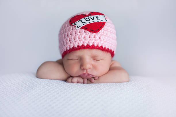 "Newborn Baby Girl Wearing a ""Love"" Hat stock photo"