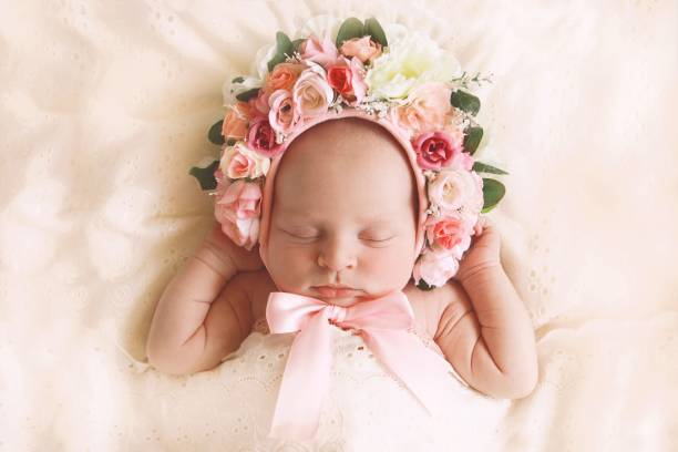 Newborn Baby Girl Wearing Floral Bonnet A newborn baby girl, fast asleep, wears a bonnet of flowers. bonnet stock pictures, royalty-free photos & images