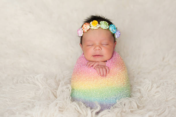 Newborn Baby Girl with Rainbow Colored Swaddle stock photo
