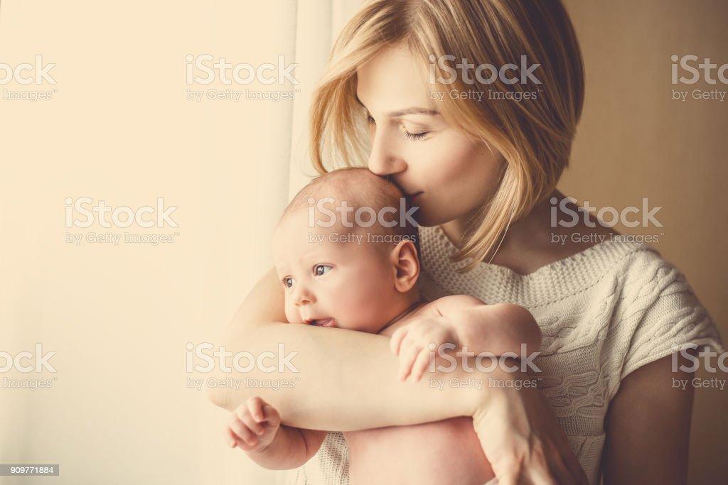 bebê recém-nascido em um tenro abraço de mãe na janela - Foto de stock de Abraçar royalty-free