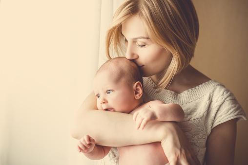 Foto de Bebê Recémnascido Em Um Tenro Abraço De Mãe Na Janela e mais fotos de stock de Abraçar