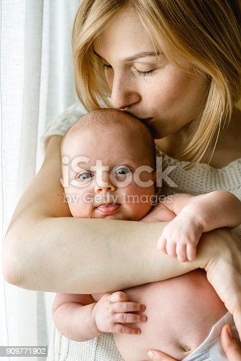909771884 istock photo newborn baby in a tender embrace of mother at the window 909771902