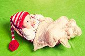 Newborn baby in a wicker basket on a green background