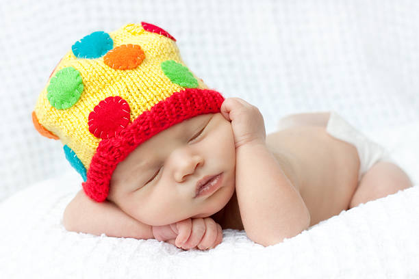 Newborn baby in colorful polka dot knit hat. stock photo