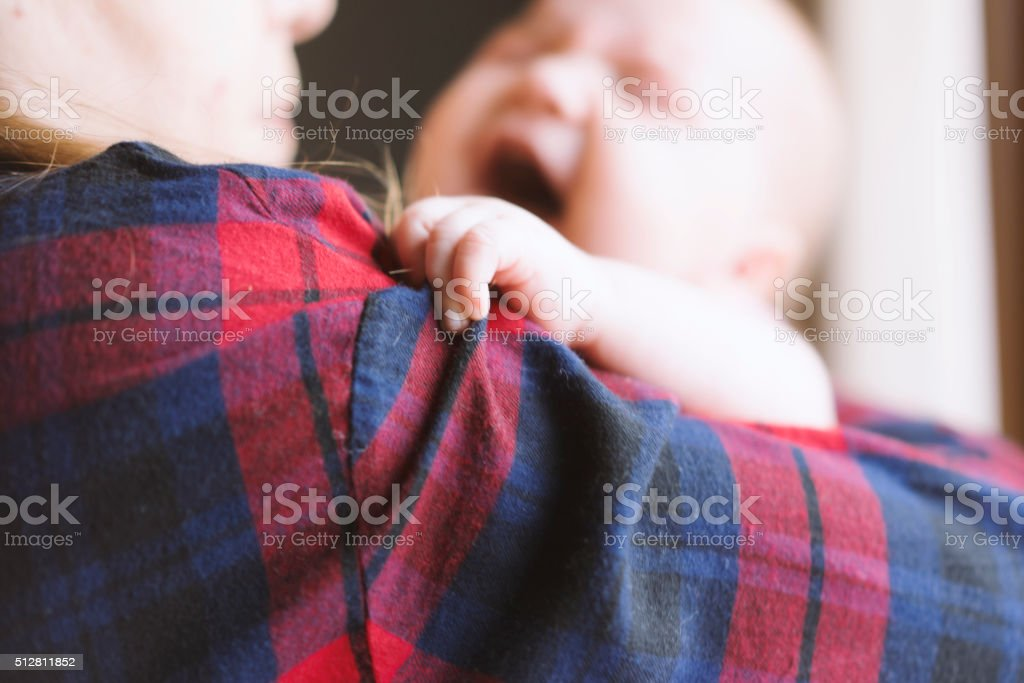 Newborn baby in her mother's arms stock photo
