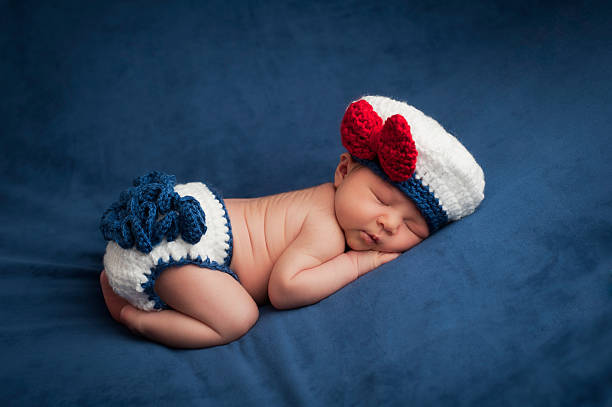 Newborn Baby in Sailor Girl Costume Eight day old newborn baby girl wearing a white and blue sailor costume. She is sleeping contentedly on her stomach. Shot in the studio on navy blue velvet. sailor hat stock pictures, royalty-free photos & images