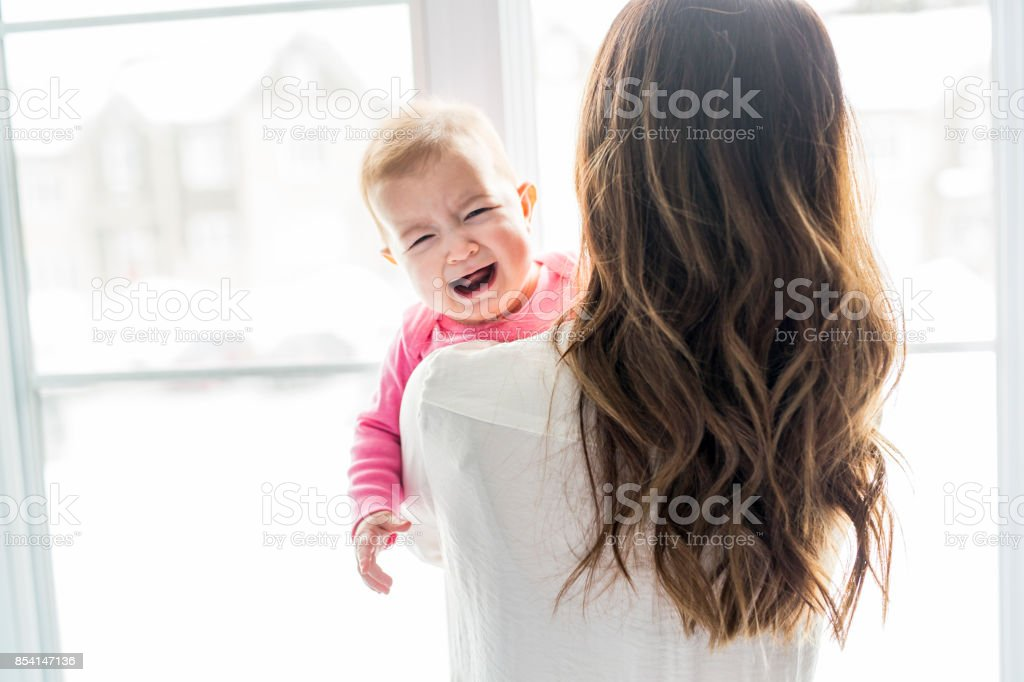 newborn baby in the hand of his mother at the window stock photo