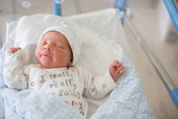 neugeborenes baby in krippe im pränatalen krankenhaus verlegen - neugeborene krankenhaus outfits stock-fotos und bilder
