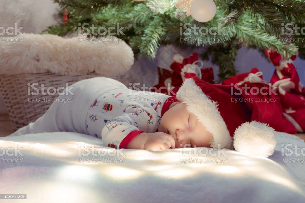 24c26663c264 Newborn baby like a gift sleeping under Christmas tree on lighting blanket. Wearing  Santa hat. - Stock image .