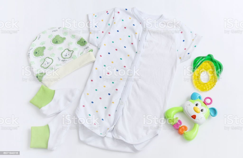 newborn baby patterned bodysuit with hat, knitwear booties and teether stock photo