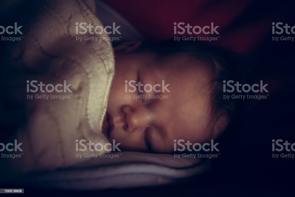 Newborn baby peaceful sleeping in dark room with low natural light covered with comfortable blanket symbolize peace and tranquility stock photo