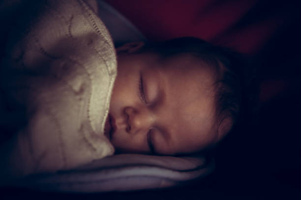 newborn baby peaceful sleeping in dark room with low natural light covered with comfortable blanket symbolize peace and tranquility - low lighting stock photos and pictures