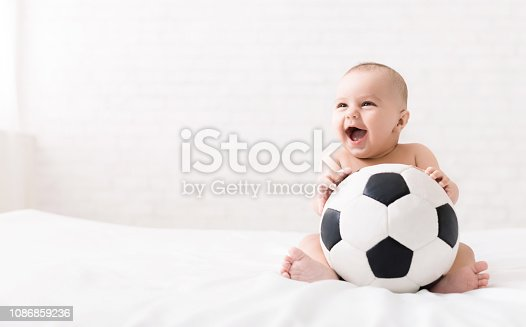 istock Newborn baby sitting with soccer ball on bed 1086859236